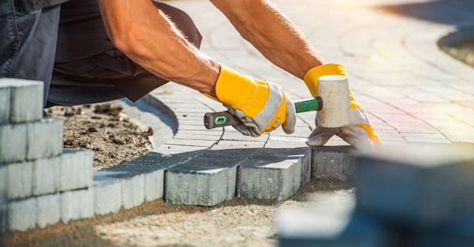 Construction worker laying paver blocks